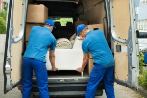 42544874 - two male workers in blue uniform adjusting sofa in truck